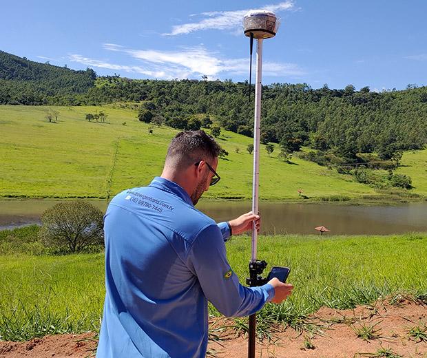 Lucas Balthazar Battochio - um homem branco, de costas, com uma camiseta azul utilizando um aparelho de topografia para fazer medições de terreno. Ao fundo uma paisagem verde com um lago, algumas árvores e arbustos.